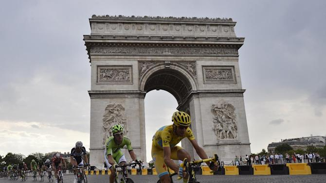 Italy's Vincenzo Nibali, wearing the overall leader's yellow jersey, rides past the Arc de Triomphe during the 137.5 km twenty-first and last stage of the 101st edition of the Tour de France cycling race between Evry and Paris on July 27, 2014