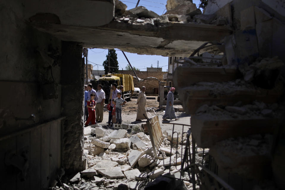 Syrians stands near the rubble of a house destroyed on Wednesday, Sept. 12, 2012 from a government airstrike, in Marea, on the outskirts of Aleppo, Syria, Thursday, Sept. 13, 2012. Four people were killed in the airstrike. (AP Photo/Muhammed Muheisen)