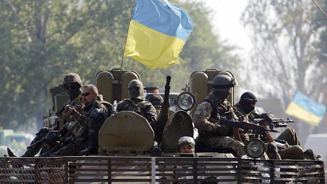 Ukrainian servicemen sit atop of an armoured personnel carrier during a patrol in Donetsk region, on September  15, 2014