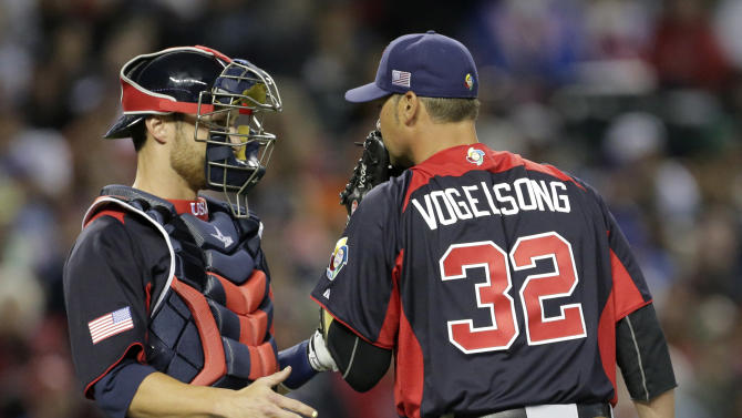 United States pitcher Ryan Vogelsong and catcher Jonathan Lucroy meet at the mound during the first inning of a World Baseball Classic game against Italy Saturday, March 9, 2013, in Phoenix. (AP Photo/Charlie Riedel)