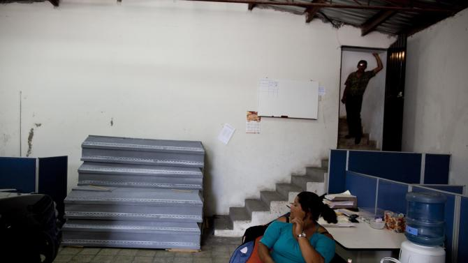 In this Aug. 17, 2012 photo, charity employees wait for customers at the offices of the Funeraria del Pueblo, or People's Mortuary, in Tegucigalpa, Honduras. The charities that provide the coffins, and sometimes free transportation and soft drinks to the bereaved, are run using public funds by three elected officials, two of whom are seeking the presidency and a third who is running for mayor of Tegucigalpa. The charities say the coffins are not a pitch for votes, but an important service to constituents who cannot afford a coffin.  (AP Photo/Esteban Felix)