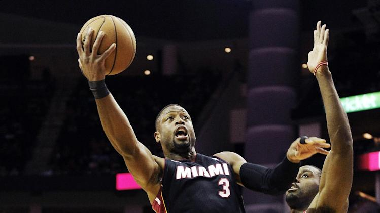 Miami Heat's Dwyane Wade (3) goes to the basket in front of Houston Rockets' Patrick Patterson (54) in the first half of an NBA basketball game, Monday, Nov. 12, 2012, in Houston. (AP Photo/Pat Sullivan)