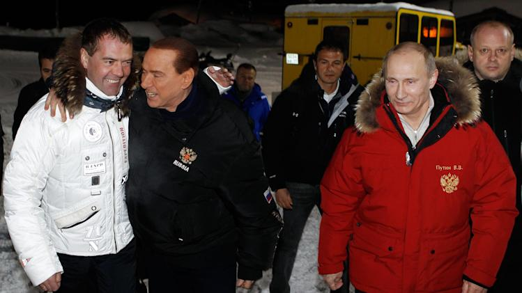 Former Italian Prime Minister Silvio Berlusconi, 2nd left, hugs Russian President Dmitry Medvedev, left, as Prime Minister Vladimir Putin, right, smiles, during their meeting in the mountain resort of Krasnaya Polyana near the Black Sea resort of Sochi, southern Russia, late Wednesday, March 7, 2012. (AP Photo/RIA-Novosti, Dmitry Astakhov, Presidential Press Service)