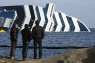 People watch the grounded cruise ship Costa Concordia off the Tuscan island of Giglio, Italy, Sunday, Jan. 22, 2012. Rescuers on Sunday resumed searching the above-water section of the capsized Costa Concordia cruise liner, but choppy seas kept divers from exploring the submerged part, where officials have said there could be bodies. Civil protection officials said that until the waves slack off, divers would not swim into the submerged part of the vessel just off the port of Giglio, a tiny Island off the Tuscan coast. (AP Photo/Pier Paolo Cito)