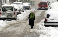 A Jordanian woman walks in a snow-covered street in Amman on January 10, 2013. A blizzard brought the country to a near halt. King Abdullah II ordered the army to help clear roads across the usually parched nation and help those stranded by the snow