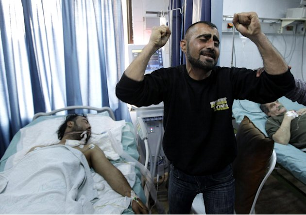 FILE - A Syrian man reacts next to his brother, who was seriously wounded during a violence between security forces and armed groups in Latakia, northwest of Damascus, Syria, on Sunday, March 27, 2011
