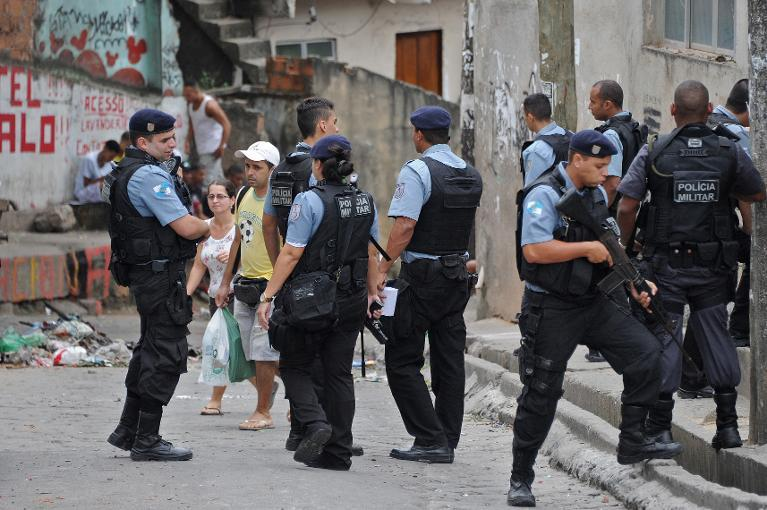 Militarized policemen patrol the streets of the  Cantagalo favela, next to Copacabana, where a young dancer was killed last weekend and residents held a protest on the eve, on April 23, 2014, in Rio de Janeiro