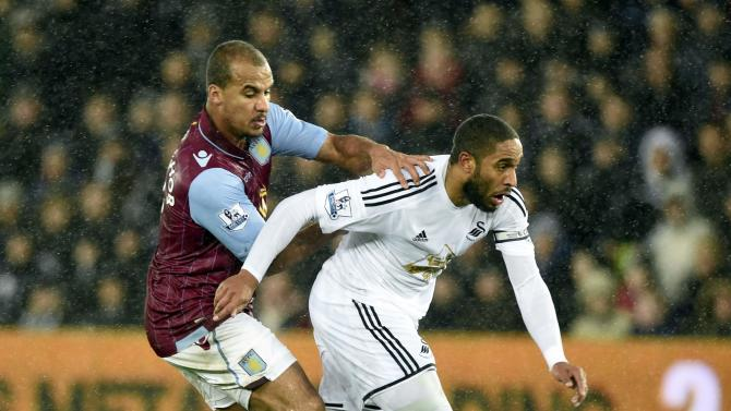 Swansea City's Ashley Williams challenges Aston Villa's Gabriel Agbonlahor during their English Premier League soccer match at the Liberty Stadium in Swansea