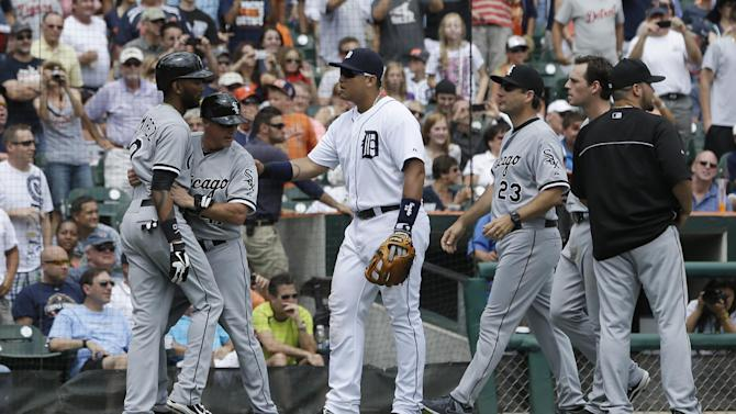 Chicago White Sox's Alexei Ramirez, left, is held back by third base coach Joe McEwing from Detroit Tigers third baseman Miguel Cabrera during the sixth inning of a baseball game in Detroit, Thursday, July 11, 2013. (AP Photo/Carlos Osorio)