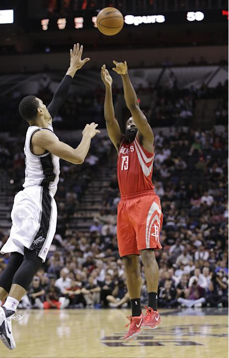 Houston Rockets' James Harden (13) shoots for three-points over San Antonio Spurs' Danny Green, left, during the second half of a preseason NBA basketball game on Thursday, Oct. 24, 2013, in San Anton