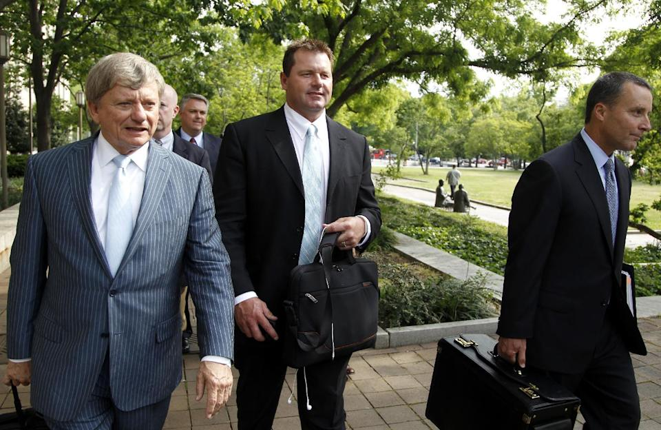 Former Major League Baseball pitcher Roger Clemens, center, leaves federal court, Tuesday, May 1, 2012, in Washington, as his retrial continues on charges of lying to Congress in 2008 when he said he had never used steroids of human growth hormone. (AP Photo/Haraz N. Ghanbari)
