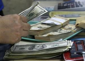 An employee counts U.S. dollar bills before changing it to Philippine Pesos inside a money changer in Manila