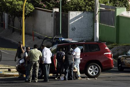 Investigators and members of a forensic team gather around a car where new tourism minister of Jalisco state Gallegos was shot dead at a crime scene between Guadalajara and Zapopan limits