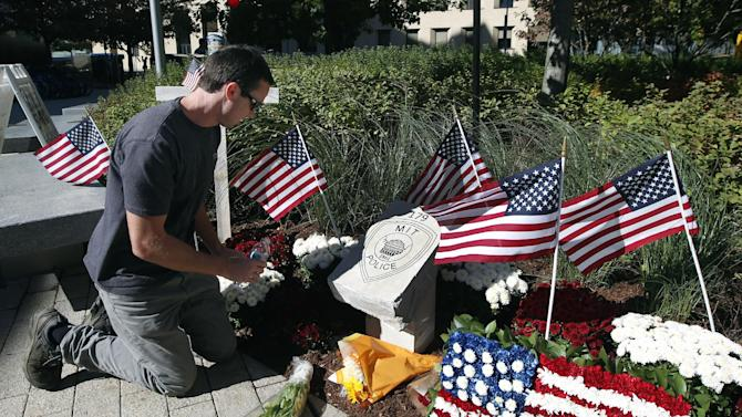 Tim Brignolo, of the Massachusetts Institute of Technology facilities department, waters the flowers at a temporary memorial to slain MIT police Officer Sean Collier in Cambridge, Mass., Friday, Oct. 18, 2013. The granite memorial was unveiled on the MIT campus Friday morning. Authorities allege the Boston Marathon bombing suspects shot and killed Collier on April 18 to get his gun as they tried to make their escape. (AP Photo/Elise Amendola)