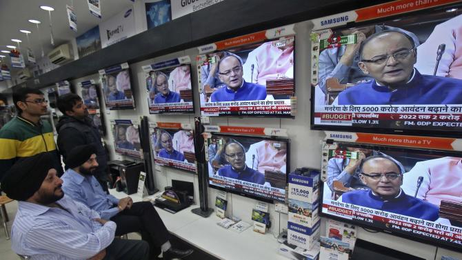 People watch television sets displaying India's FM Jaitley presenting the budget in parliament at an electronic shop in Chandigarh
