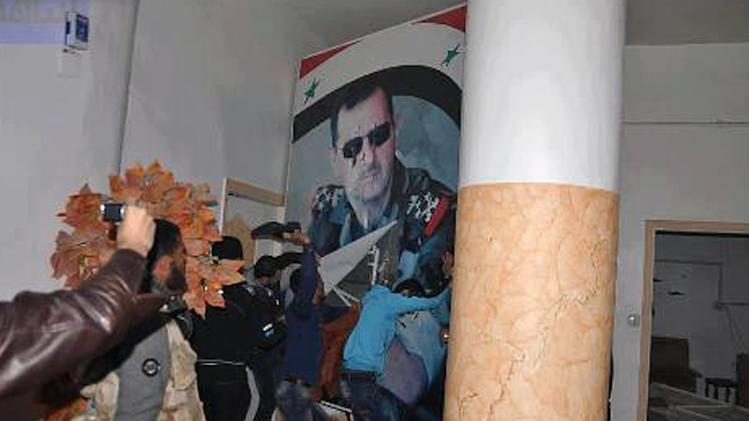 FILE - In this Monday, March 4, 2013 file photo citizen journalism image provided by Coordination Committee in Kafr Susa which has been authenticated based on its contents and other AP reporting, shows people tearing down a huge poster of President Bashar Assad and hitting it with their shoes, in Raqqa, Syria. A quiet power struggle in taking place in the eastern city between Islamic extremist rebels, who control the city after capturing it four months ago from the regime, and moderates trying to curtail their influence, making it a test case for the opposition.(AP Photo/Coordination Committee In Kafr Susa, File)