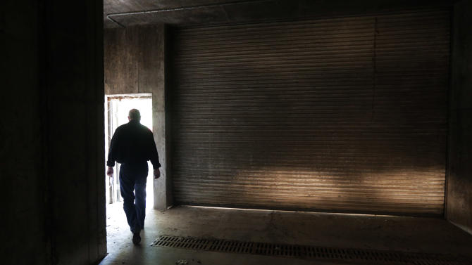 A reporter walks through a door to the Vivos Shelter and Resort during a tour of the facility in Atchison, Kan., Tuesday, June 18, 2013. (AP Photo/Orlin Wagner)