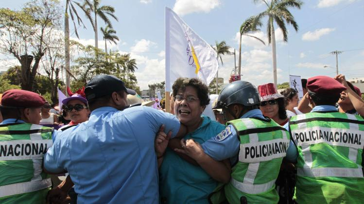 A feminist activist tries to cross a police barricade during an International Women's Day march in Managua