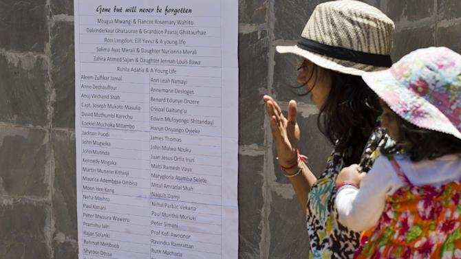Relatives of Westgate attack victim Mitul Shah observe a list of names of some of those who died, at a memorial service marking the one-month anniversary of the Sept. 21 Westgate Mall terrorist attack, in Karura Forest in Nairobi, Kenya Monday, Oct. 21, 2013. Families and friends of those killed in the attack planted trees in memory of lost loved ones in a ceremony that stressed that the attack occurred against people of all races and religions. (AP Photo/Ben Curtis)