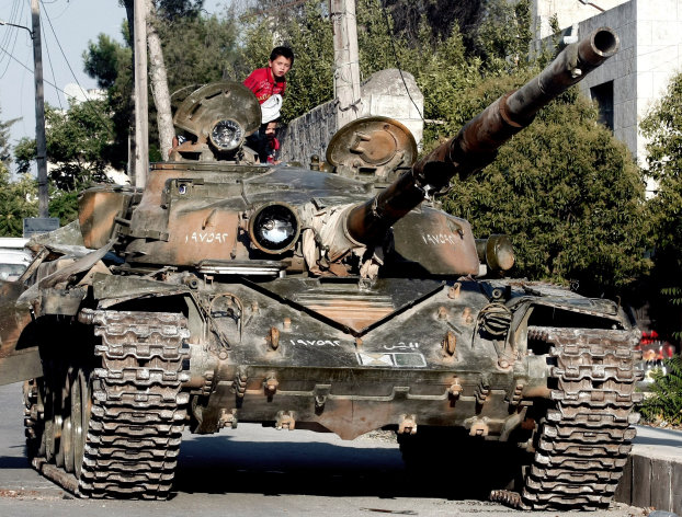 In this Tuesday, July 24, 2012 photo, a Syrian boy sits atop a damaged military tank at the border town of Azaz, some 20 miles (32 kilometers) north of Aleppo, Syria. Turkey sealed its border with Syria to trucks on Wednesday, July 25, 2012 cutting off a vital supply line to the embattled nation as fighting stretched into its fifth day in the commercial capital of Aleppo. (AP Photo/Turkpix)