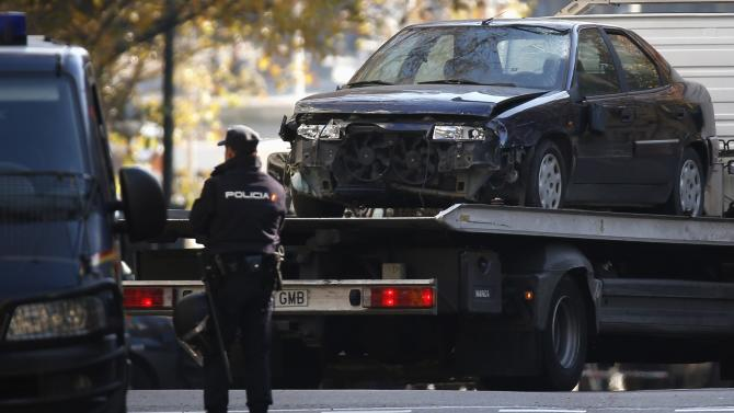 A police officer stands guard as the car that was driven into the headquarters of Spain's ruling People's Party is towed away in Madrid