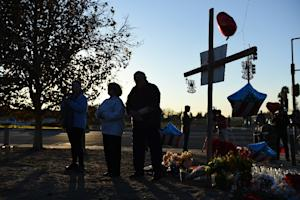 People pray at a makeshift memorial for the victims…