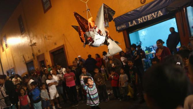 "A girl prepares to hit a pinata during a traditional Mexican Christmas celebration known as ""Posada mexicana"" at La Merced neighbourhood in Mexico City"