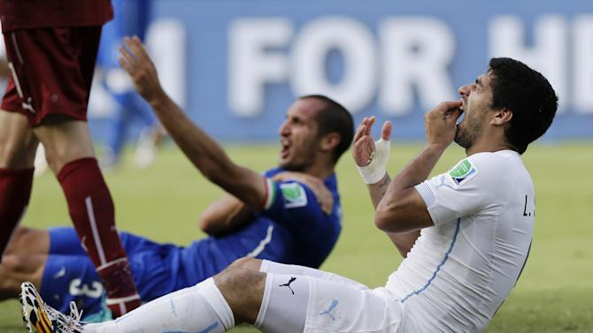Uruguay's Luis Suarez holds his teeth after running into Italy's Giorgio Chiellini's shoulder