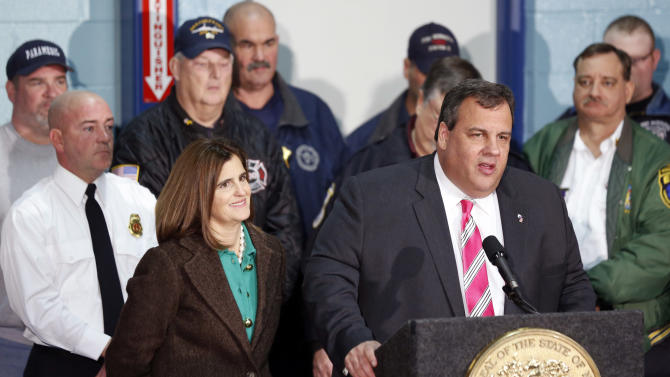 "New Jersey Gov. Chris Christie, right, stands next to his wife, Mary Pat Christie, left, and a group of first responders while talking during a news conference at at fire house, Monday, Nov. 26, 2012, in Middletown, N.J. Christie announced he will seek re-election to a second term. Christie says he want New Jerseyans to know that he's ""in this for the long haul"" as he leads the state's recovery from Superstorm Sandy.  (AP Photo/Julio Cortez)"