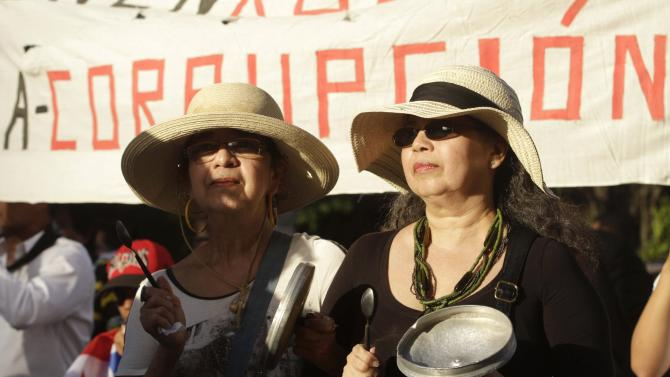 Women hit pans during an anti-corruption march and a protest against Ricardo Martinelli in Panama City