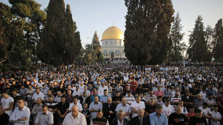 Muslim worshippers take part in a prayer in front of the Dome of the Rock during the holiday of Eid al-Fitr in Jerusalem