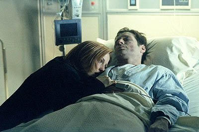 "Scully (Gillian Anderson) at the bedside of an ailing Fox Mulder (David Duchovny) in the ""Deadalive"" episode of Fox's The X-Files X-Files"