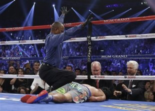 Referee Kenny Bayless calls the fight as he kneels over Manny Pacquiao. (AP)