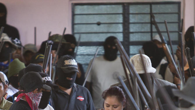 Masked members of the community of Ayutla escort a detained woman to a community assembly in the town of El Meson, Mexico, Thursday Jan. 31, 2013. Vigilantes who have taken up arms against drug cartel violence and common crime in southern Mexico brought charges ranging from organized crime to kidnapping and extortion against 50 men and three women who they have been holding prisoner at improvised jails, in some cases for weeks. (AP Photo/Christian Palma)