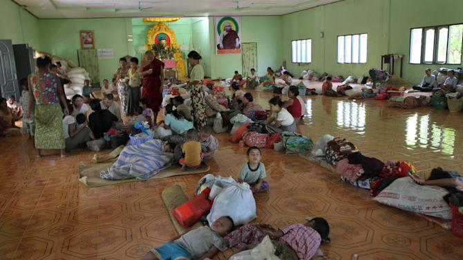 In this photo taken on Nov. 8, 2012, Ethnic Rakhine people take refuge at a monastery in Mrauk-U, Rakhine state, western Myanmar. Mrauk-U itself has been spared the bloodshed between the Buddhist Rakhine and the Muslim Rohingya that has scarred other parts of Rakhine state. It is calm, and for foreign tourists, safe. But just 10 kilometers (six miles) to the south, there is a village where civilians were reportedly beheaded in a massacre last month that saw women and children slaughtered, then buried in mass graves. Across western Myanmar's Rakhine state, the United Nations is distributing emergency supplies of food and shelter to terrified villagers who have fled burning homes. A nighttime curfew is in force. (AP Photo/Khin Maung Win)