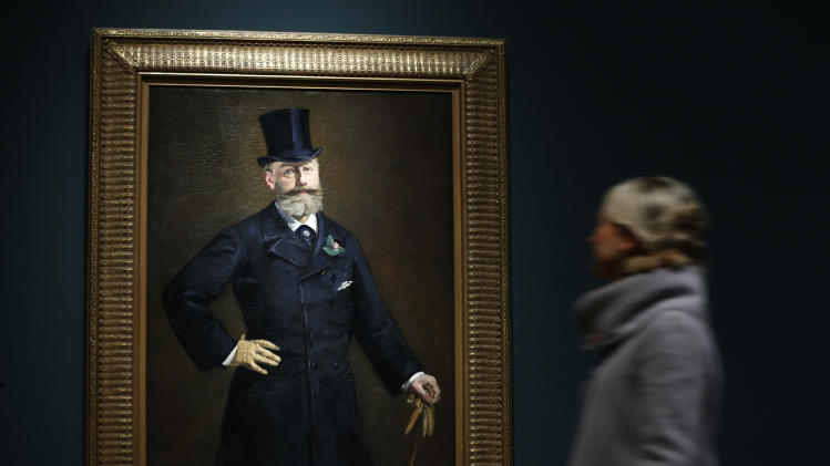 A Royal Academy of Arts employee walks past Manet's oil on canvas painting entitled 'Portrait of M. Antonin Proust, 1880' as she poses for photographers at the gallery in central London, Tuesday, Jan. 22, 2013. The Royal Academy's major exhibition 'Manet: Portraying Life', that will run from Jan. 26 to April, 14, 2013, features over 50 paintings spanning the career of the modern artist. The exhibition examines the relationship between Manet's portrait painting and his scenes of modern life. (AP Photo/Lefteris Pitarakis)