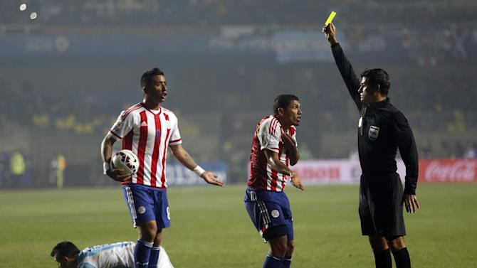 Referee Sandro Ricci, from Brazil, shows a yellow card to Paraguay's Richard Ortiz after he fouled Argentina's Sergio Aguero , right, during a Copa America semifinal soccer match at the Ester Roa Rebolledo Stadium in Concepcion, Chile, Tuesday, June 30, 2015. Argentina beat Paraguay 6-1 in the Copa America semifinals on Tuesday, setting up a final against host Chile.(AP Photo/Silvia Izquierdo)