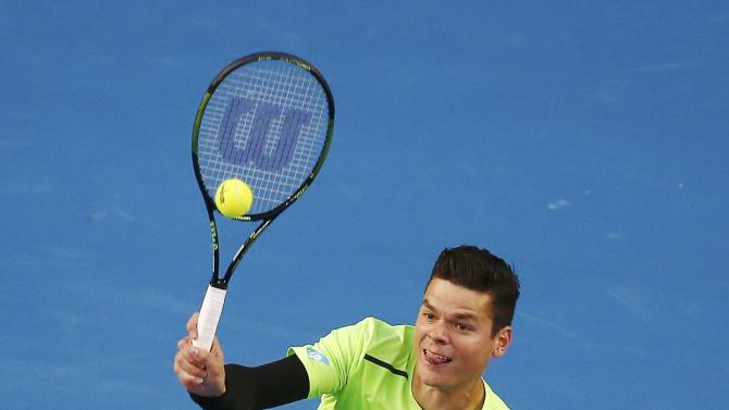Raonic of Canada hits a return to Lopez of Spain during their men's singles match at the Australian Open 2015 tennis tournament in Melbourne