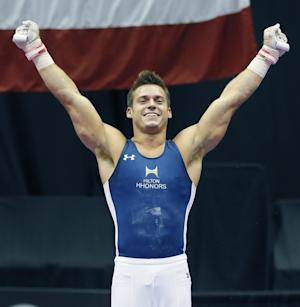 Sam Mikulak smiles after hitting his landing on the rings part of the competition at the U.S. men's gymnastic championships on Sunday, Aug. 24, 2014, in Pittsburgh. Mikulak won the overall championship. (AP Photo/Keith Srakocic)
