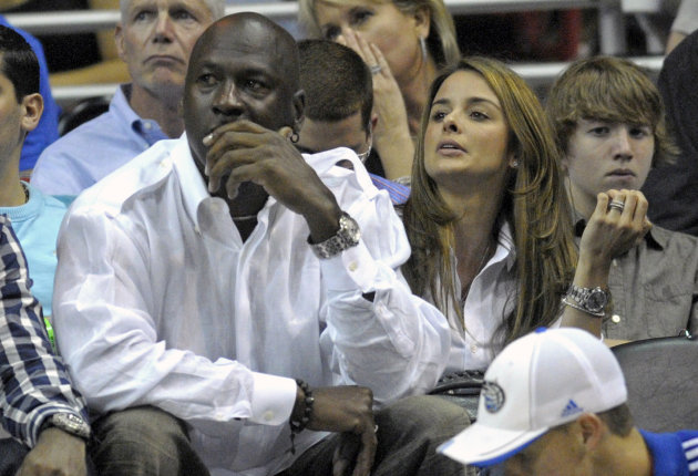 FILE - In this April 21, 2010,  file photo, Michael Jordan and Yvette Prieto, right, watch the second half of Game 2 of a first round NBA basketball playoff game between the Orlando Magic and the Char