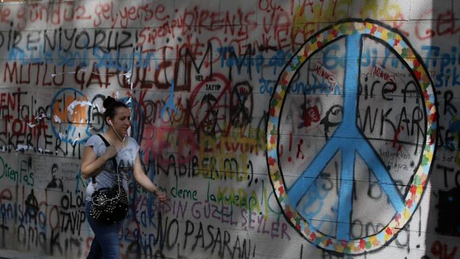 """A woman walks past graffiti sprayed by Turkish protesters during the demonstration in Kugulu Park in Ankara, Turkey, Thursday, June 13, 2013. Turkey's prime minister issued a """"final warning"""" to protesters on Thursday, demanding that they end their occupation of a park next to Istanbul's landmark Taksim Square. (AP Photo/Burhan Ozbilici)"""