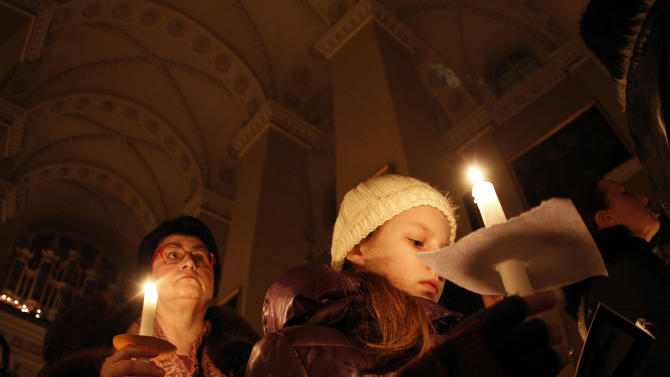 Worshippers hold candles during the Easter vigil mass in Cathedral-Basilica at the Vilnius, Lithuania, Saturday, March 30, 2013. (AP Photo/Mindaugas Kulbis)