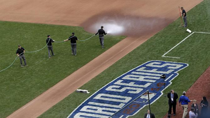 The grounds crew water down the area near first base before Game 4 of baseball's World Series between the Kansas City Royals and the San Francisco Giants on Saturday, Oct. 25, 2014, in San Francisco. When it comes to the speedy Royals' running game, Kansas City manager Ned Yost thinks the San Francisco Giants are being sticks in the mud. The area around first base appeared to be a bit mucky for Game 3 of the World Series on Friday night. The Royals appeared to conclude the dirt was hosed down with extra vigor. (AP Photo/Marcio Jose Sanchez)