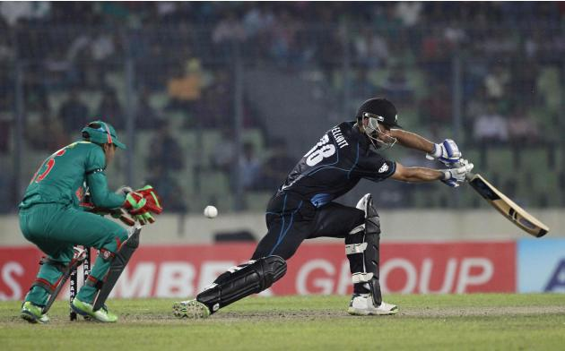 New Zealand's Grant Elliott plays a shot as Bangladesh's captain and wicket keeper Mushfiqur Rahim tries to catch during their first ODI cricket match in Dhaka