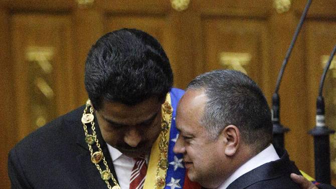 President of the National Assembly Diosdado Cabello embraces Nicolas Maduro after Maduro was sworn in as Venezuela's president at a ceremony in the National Assembly in Caracas, Venezuela, Friday, March 8, 2013. Maduro was sworn in Friday as Venezuela's acting president, against the objections of the political opposition who said the move violated the country's constitution.  Late President Hugo Chavez designated Vice President Maduro as his successor before he died Tuesday of cancer. (AP Photo/Fernando Llano)