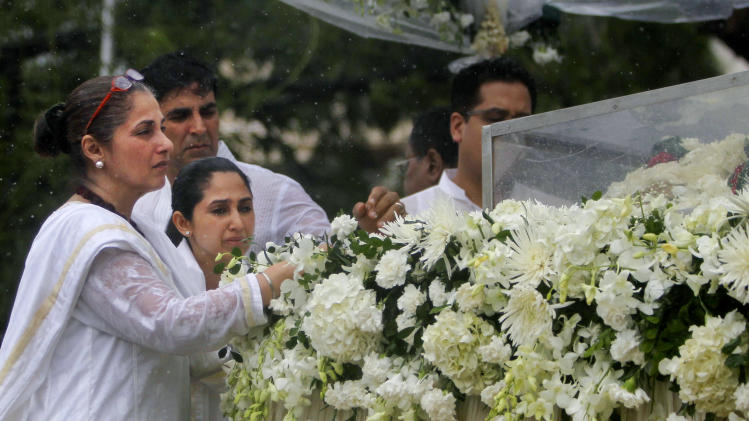 Actress Dimple Kapadia, the wife of late Bollywood superstar Rajesh Khanna, left, along with her daughter Rinke Khanna, second from left and son-in-law, actor Akshay Kumar, background left, pay their respects during Khanna's funeral in Mumbai, India, Thursday, July 19, 2012. Khanna, whose success as a romantic lead in scores of Indian movies made him Bollywood's first superstar, died Wednesday after a brief illness. He was 69. (AP Photo/Rafiq Maqbool)