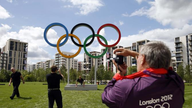 File photo of a volunteer taking a photograph of the Olympic rings at the Athletes' Village at the Olympic Park in London