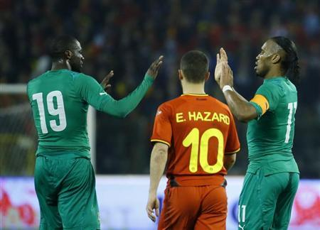 Ivory Coast's Didier Drogba (R) celebrates with teammate Yaya Toure (L) after scoring a goal against Belgium as Belgium's Eden Hazard (C) looks on during their international friendly soccer ma