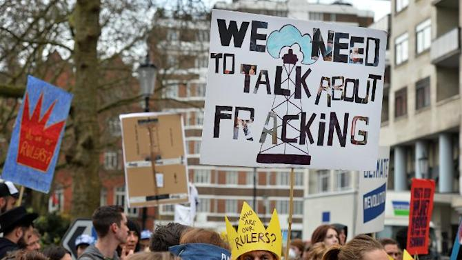 Demonstrators carry placards as they gather for an anti-fracking protest in London on March 19, 2014