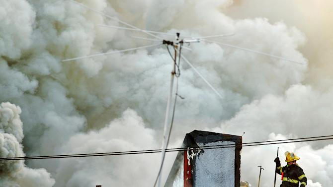 A firefighter battles a blaze that burned a fabric shop, upstairs apartments and a neighboring boutique in Philadelphia on Saturday, April 6, 2013. The fire caused a partial roof collapse that killed a firefighter and injured a colleague who was trying to rescue him, officials said. (AP Photo/Peter Tobia)